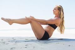 Fit blonde in core balance pilates pose on the beach - stock photo