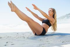 Stock Photo of Fit blonde in core balance pilates pose on the beach
