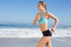 Fit woman jogging on the beach - stock photo