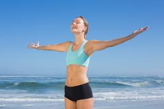 Fit woman standing on the beach with arms out - stock photo