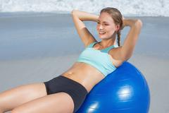 Fit woman lying on exercise ball at the beach doing sit ups - stock photo