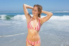 Stock Photo of Blonde fit woman in striped bikini at beach smiling