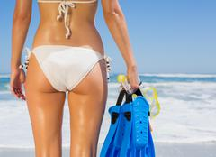 Stock Photo of Fit woman in white bikini holding snorkeling gear on the beach