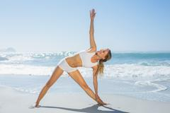 Gorgeous blonde standing in extended triangle pose by the sea - stock photo