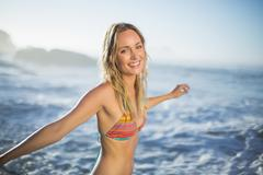 Content blonde standing on the beach in bikini with arms out Stock Photos