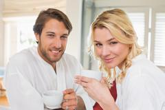 Cute couple in bathrobes having coffee together smiling at camera - stock photo