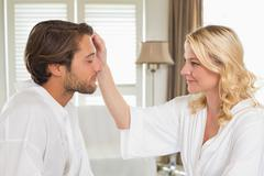 Cute couple in bathrobes spending time together - stock photo