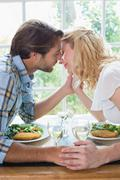 Stock Photo of Cute affectionate couple having a meal together