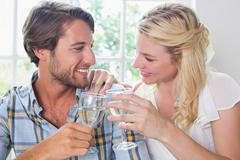 Stock Photo of Cute smiling couple enjoying white wine together