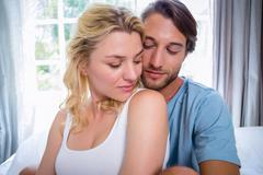 Stock Photo of Cute young couple relaxing on bed together