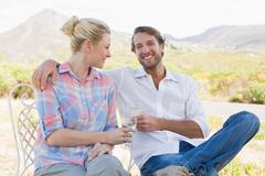 Stock Photo of Cute couple sitting in the garden enjoying wine together