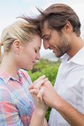 Cute affectionate couple standing outside holding hands Stock Photos