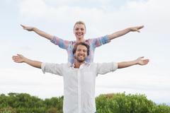 Cute couple standing outside with arms outstretched - stock photo