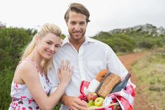 Cute couple going for a picnic smiling at camera - stock photo
