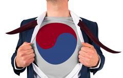 Businessman opening shirt to reveal korea republic flag - stock photo
