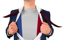 Businessman opening shirt to reveal france flag - stock photo