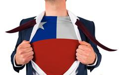 Businessman opening shirt to reveal chile flag - stock photo