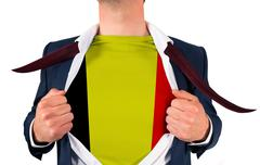 Businessman opening shirt to reveal belgium flag - stock photo