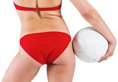Fit girl in bikini holding football Stock Photos
