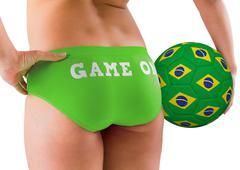 Fit girl in green bikini holding brasil football - stock photo