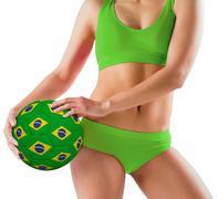 Stock Photo of Fit girl in green bikini holding brazil ball