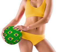 Stock Photo of Fit girl in yellow bikini holding brazil football