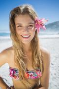 Beautiful smiling blonde with flower hair accessory on the beach - stock photo