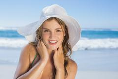 Beautiful girl in white straw hat smiling at camera on beach - stock photo