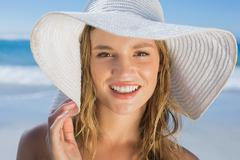 Stock Photo of Beautiful girl in straw hat on the beach smiling at camera