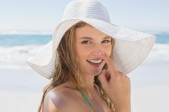 Stock Photo of Beautiful girl putting spf on nose on the beach smiling at camera