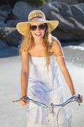 Beautiful smiling blonde in sundress on bike at the beach - stock photo