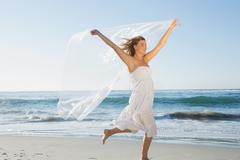 Stock Photo of Beautiful smiling blonde in white sundress on the beach with scarf