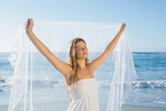 Stock Photo of Beautiful calm blonde in white sundress on the beach with scarf