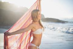 Beautiful smiling blonde holding scarf at the beach - stock photo