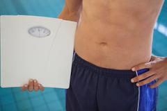 Fit man in swimming trunks standing by the pool holding weighing scales - stock photo