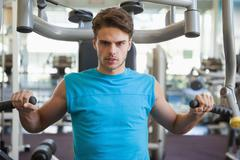 Stock Photo of Focused man using weights machine for arms