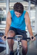 Focused fit man on the spin bike Stock Photos