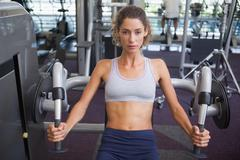 Stock Photo of Fit woman using the weights machine for her arms