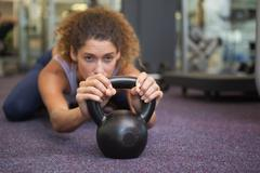 Fit woman lying with kettlebell - stock photo
