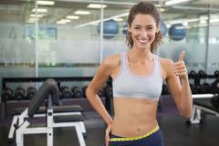 Stock Photo of Fit woman measuring her waist and showing thumb up
