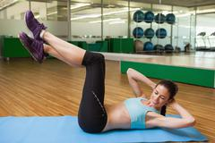 Stock Photo of Fit brunette doing sit ups in fitness studio