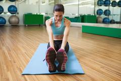 Stock Photo of Fit brunette warming up in fitness studio