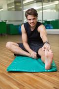 Fit smiling man warming up in fitness studio Stock Photos