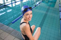 Stock Photo of Fit swimmer sitting by the pool smiling at camera