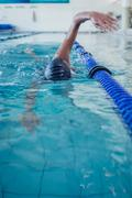 Fit swimmer doing the front stroke in the swimming pool - stock photo
