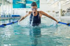 Fit swimmer doing the butterfly stroke in the swimming pool - stock photo