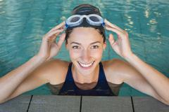 Fit swimmer smiling up at camera in the swimming pool - stock photo