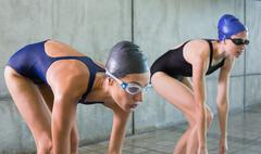 Female swimmers about to dive in the swimming pool Stock Photos