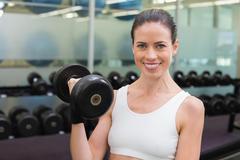 Stock Photo of Fit smiling brunette lifting heavy black dumbbell