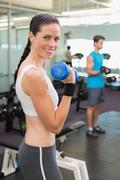 Stock Photo of Fit brunette lifting blue dumbbell smiling at camera